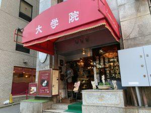 赤い看板が目印で大学院と書いてあるか喫茶店。