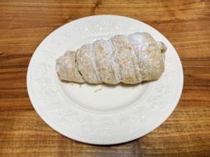 粉糖をまぶした美味しそうなパイ生地のコロネ。